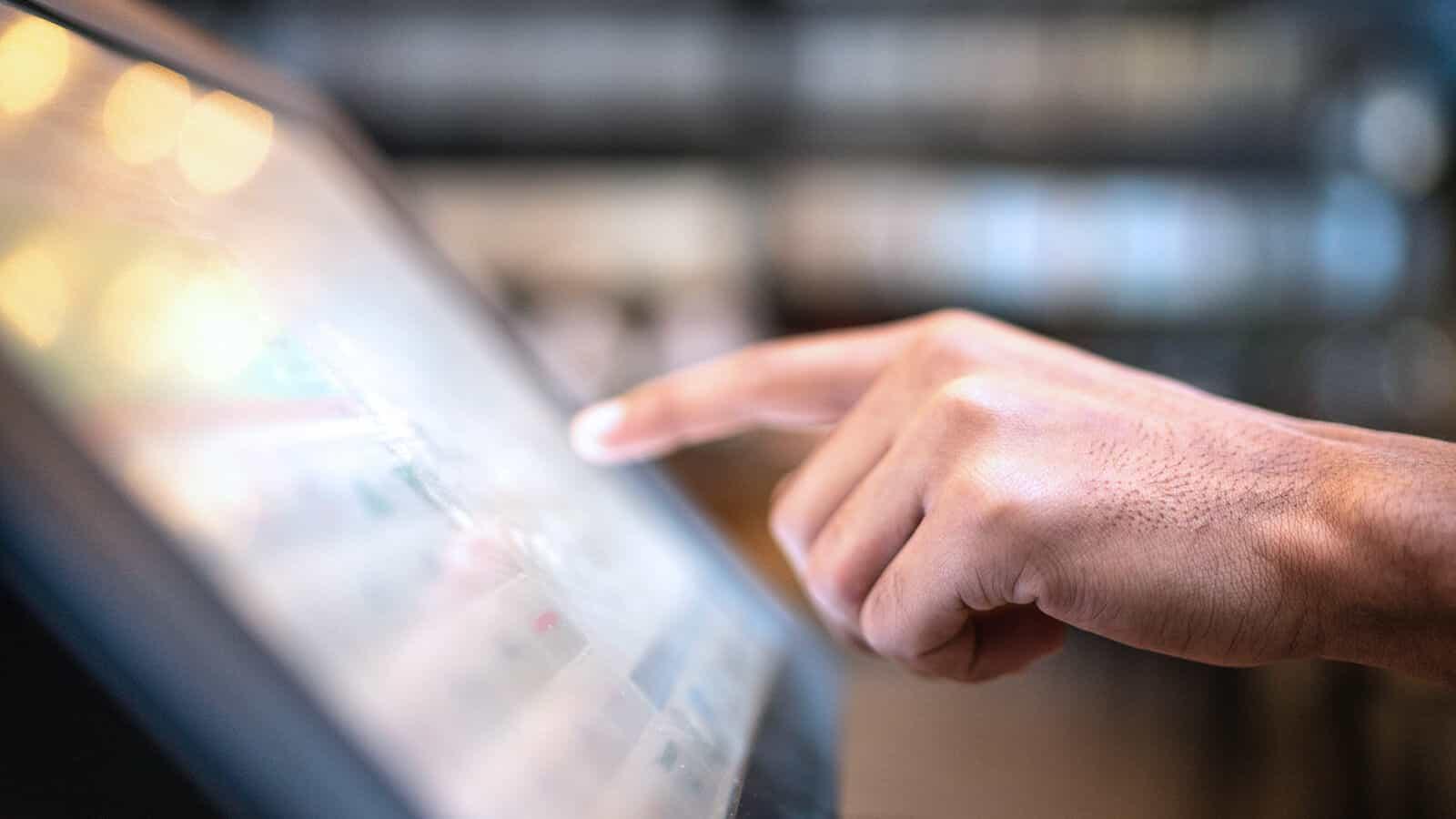 Hand tippt auf Monitor von Kasse