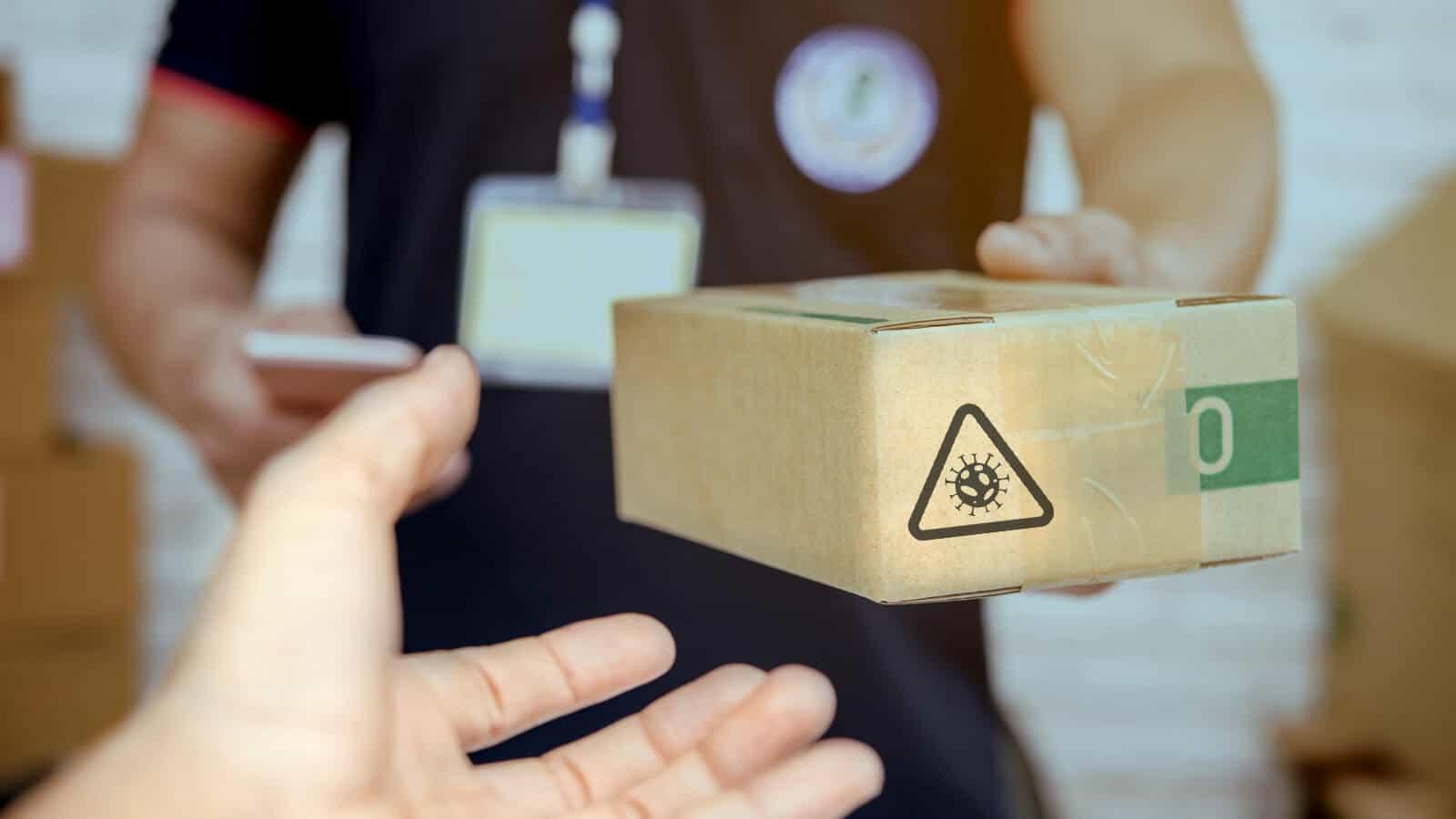 Paket mit Corona-Warnsymbol wird übergeben